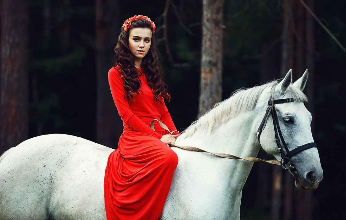 photo of woman riding on white horse