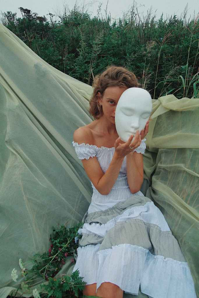 sitting woman wearing gray off shoulder dress holding mask